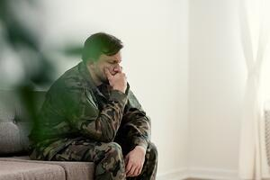 Sad-soldier-in-uniform-covering-his-mouth-while-sitting-on-a-sofa-1019966974_1258x838